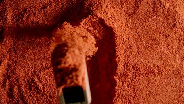 vídeos y material grabado en eventos de stock de vista superior: el polvo de pimienta roja se toma con una cuchara de madera - cayena guindilla roja