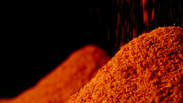 SLOW MOTION:Red pepper powder pouring in a heap
