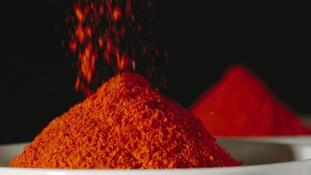 vídeos y material grabado en eventos de stock de polvo de pimiento rojo vertiendo en un tazón blanco, de cerca, a cámara lenta - cayena guindilla roja