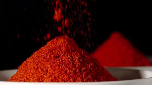 vídeos y material grabado en eventos de stock de slow motion: polvo de pimiento rojo que vierte en un tazón blanco-close up - cayena guindilla roja