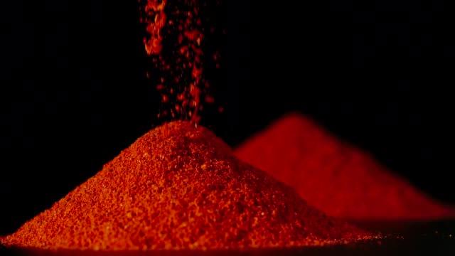 vídeos y material grabado en eventos de stock de slow motion: polvo de pimienta roja que vierte sobre una mesa-close up - cayena guindilla roja