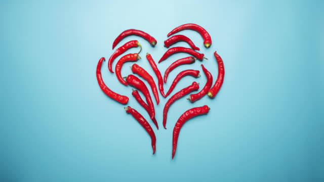 red peppers forming heart shape on studio blue background - peperoncino video stock e b–roll