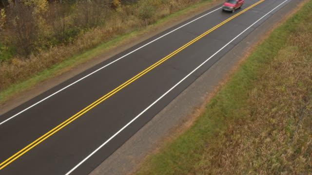 vídeos de stock, filmes e b-roll de antena: picape vermelha de condução na estrada vazia através da paisagem rural - caminhonete pickup