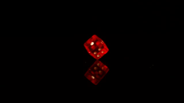 Red plastic dice revolving on black background video