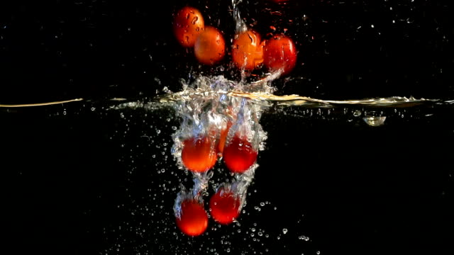 Red Plum. Fruits falling into Water against. Black Background.Slow Motion Slow Motion. Fruit falling into Water. plum stock videos & royalty-free footage