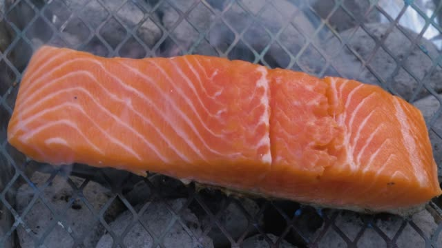 vídeos de stock e filmes b-roll de red raw fillet of salmon or trout fish is baking on grill with smoke. slow motion - assado no forno