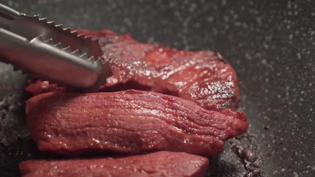 röd rå fläsk blir grillad på en svart kastrull. vändning. läckra. vissa brände. - frying pan bildbanksvideor och videomaterial från bakom kulisserna