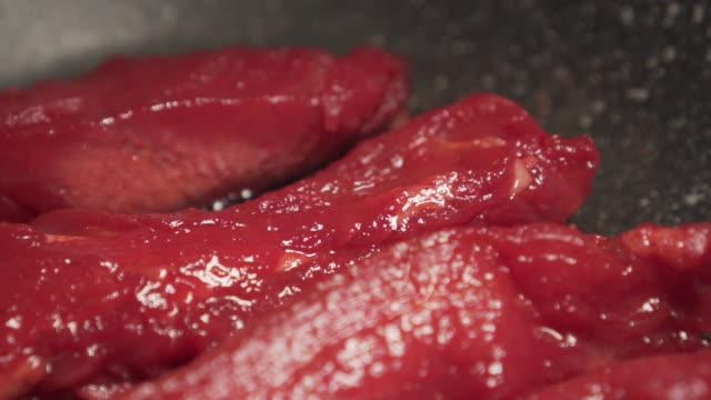 röd rå fläsk blir grillad på en svart kastrull. börjar laga mat. läckra. matlagning. - frying pan bildbanksvideor och videomaterial från bakom kulisserna
