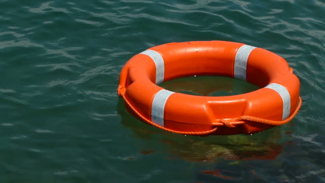 A red rescue buoy floating on the water surface video