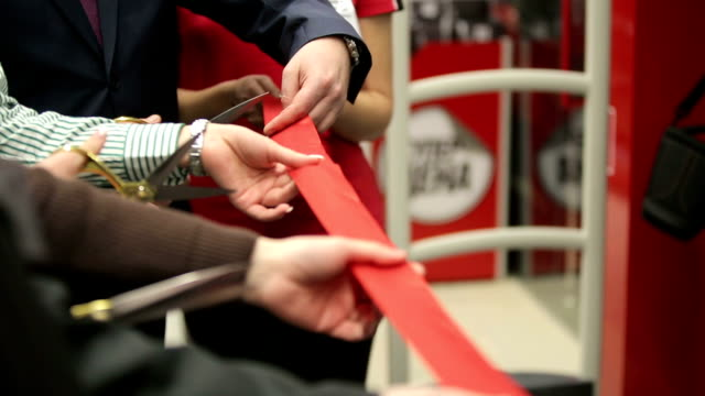 stockvideo's en b-roll-footage met red ribbon cutting scissors in hands - openingsevenement