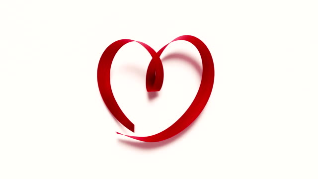 Red Ribbon Forming A Heart Shape On White Background 4K Resolution