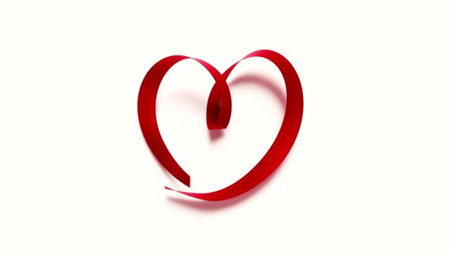 레드 리본 흰색 배경 4 k 해상도에 심장 모양 형성 - ribbon 스톡 비디오 및 b-롤 화면