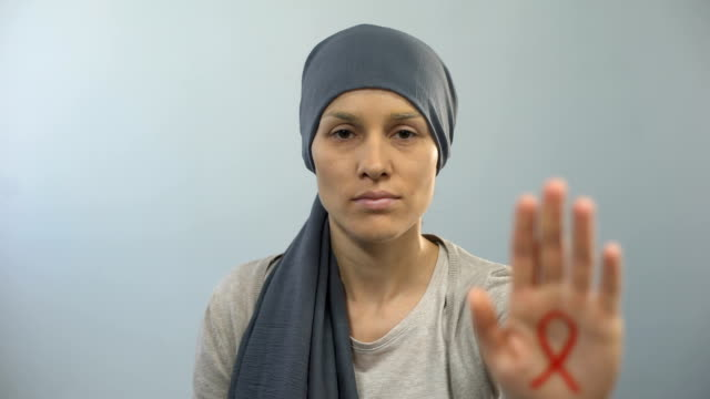 Red ribbon sign on womans palm showing stop gesture, AIDS awareness campaign video