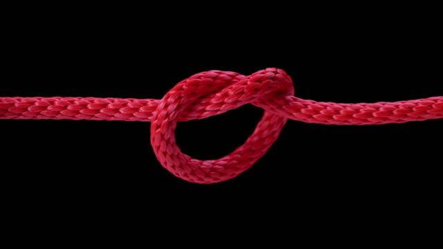 slo mo ld rotes seil zu einem knoten angezogen - kürzer als 10 sekunden stock-videos und b-roll-filmmaterial