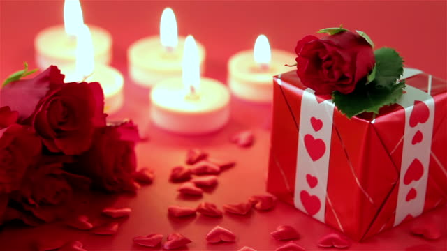 Red roses and gift box on red background video