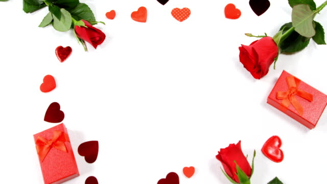 red roses, gift boxes and heart shape of confetti on white surface in circle formation 4k - simbolo concettuale video stock e b–roll