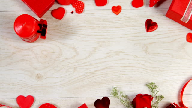 red roses, gift boxes and heart shape of confetti on wooden surface 4k - simbolo concettuale video stock e b–roll
