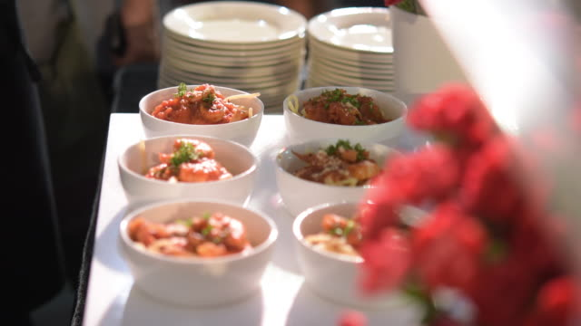 Red sauce spaghetti in small bowls arrange in row for serving in party