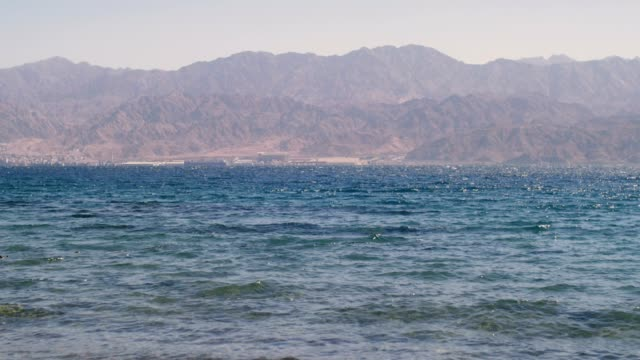 red sea water with jordan's mountains in the horizon - paesi del golfo video stock e b–roll