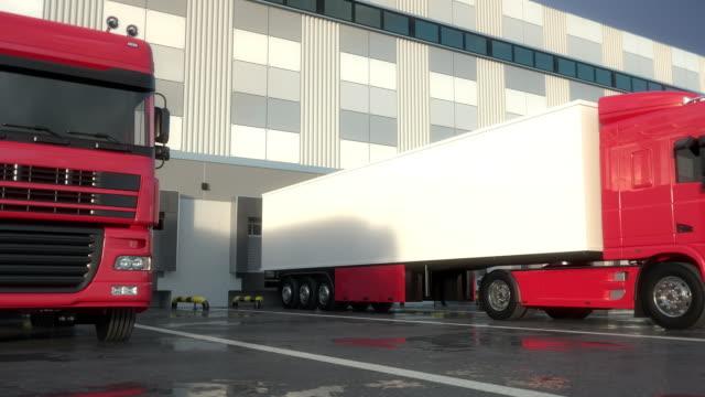 Red semi-trailer trucks docking onto warehouse loading dock. Seamless Loop