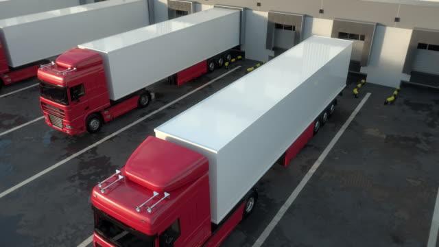 red semi-trailer trucks docking onto warehouse loading dock. seamless loop - rozładowywać filmów i materiałów b-roll