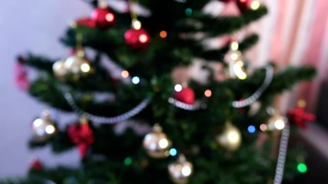 Red shiny balls and gold toys on the branches of Christmas tree. Christmas garland with lights on the Christmas tree.