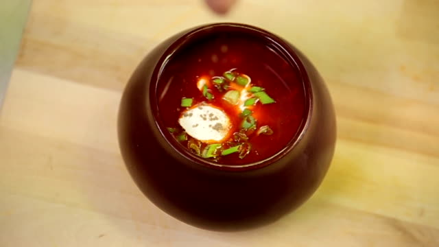 Red soup borsch with sourcream being prepaired and served at the restaurant kitchen video