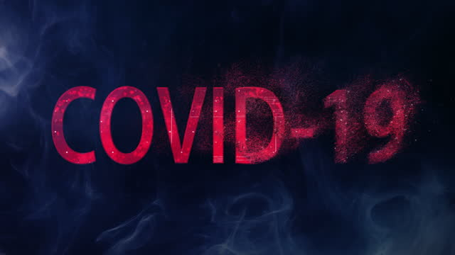 Red, sparkling word 'Covid-19' on dark background. Disappearing disease metaphor
