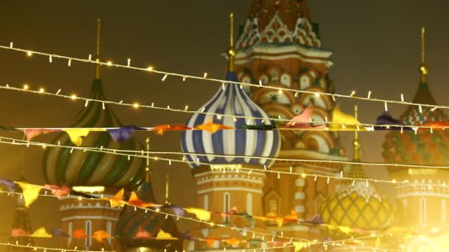 röda torget inredda för nyår och jul firande. färgglada flaggor och glödlampor, berömda st.basil katedralen på bakgrund. moscow, ryssland - vasilijkatedralen bildbanksvideor och videomaterial från bakom kulisserna