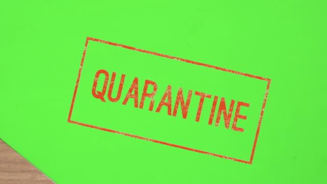 vídeos de stock e filmes b-roll de red stamp quarantine on paper chroma key green screen - vírus informático
