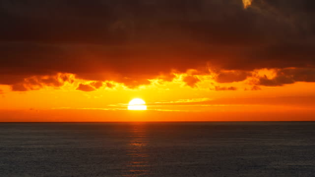 Red sunrise over water surface time lapse Red sunrise dawn over sea water surface and clouds time lapse dawn stock videos & royalty-free footage