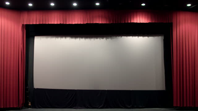 Red theater curtain opens to reveal cinema screen HD video