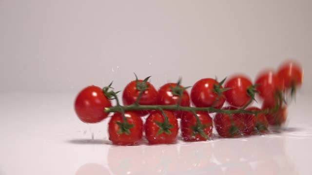 Red tiny tomatoes falling in water on white table in white wall background. Slow Motion 240 fps - vídeo
