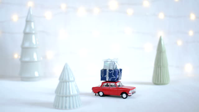 red toy car with a christmas tree on the roof, garland bokeh on the background - christmas background стоковые видео и кадры b-roll