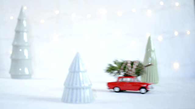 red toy car with a christmas tree on the roof - christmas background стоковые видео и кадры b-roll