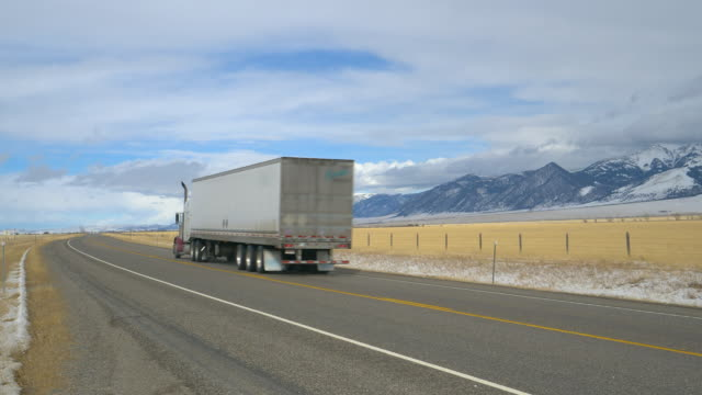 Red truck hauls cargo across picturesque Montana wilderness on cold winter day.