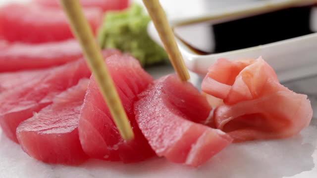 Red Tuna Sashimi Chospticks take a  red tuna sashimi piece and dip it in soy sauce. sashimi stock videos & royalty-free footage