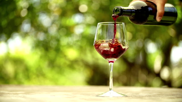 Red wine being filled into glass Red wine being filled into glass in slow motion on outdoor table red wine stock videos & royalty-free footage