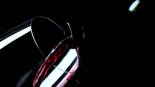 Red wine being poured into a glass, black, closeup, slowmotion video