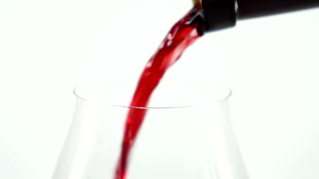 Red wine being poured into wine glass, white, slowmotion, closeup video