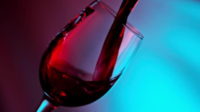 rotwein bildet schöne welle. rotwein aus flasche ins glas gießen - cabernet sauvignon traube stock-videos und b-roll-filmmaterial