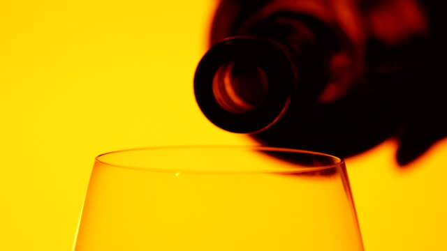 Red wine is being poured into a glass, yellow, closeup, slowmotion video