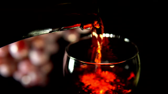 Red wine is poured into a glass on a dark background video