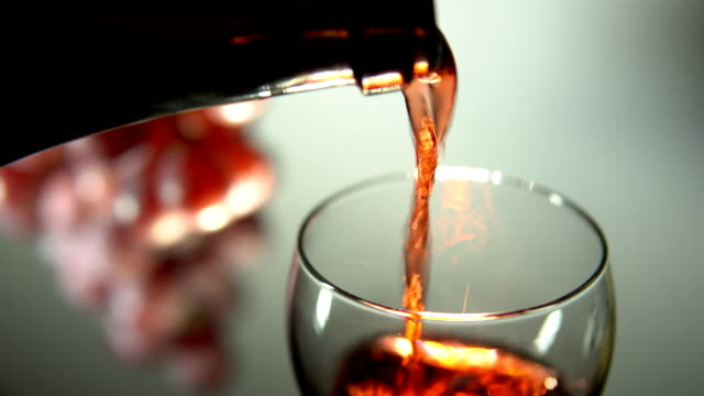 Red wine is poured into a glass on a light background. video