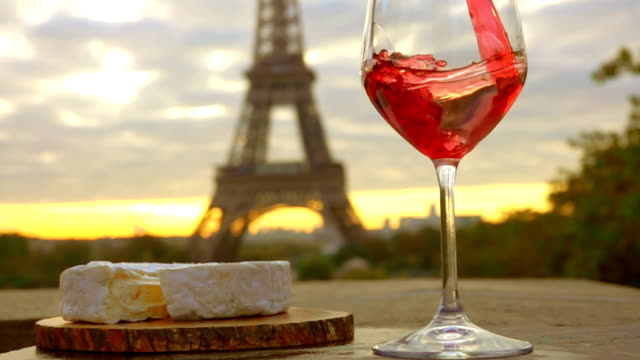 Red wine is poured into glass next to Eiffel Tower