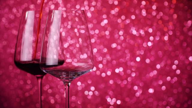 赤ワインはボケの背景にグラスに注がれます。ワイングラスに赤ワインを詰めるクローズアップ。スローモーションショット。4k。 - 赤ワイン点の映像素材/bロール