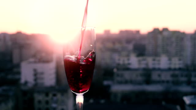 Red wine poured into a glass in slow motion at sunset video