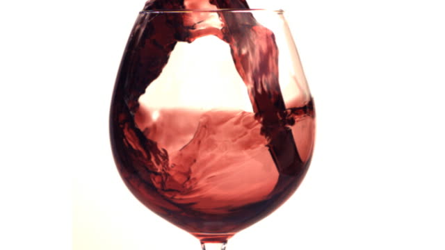 Red wine poured into a glass in slow motion. HD. video