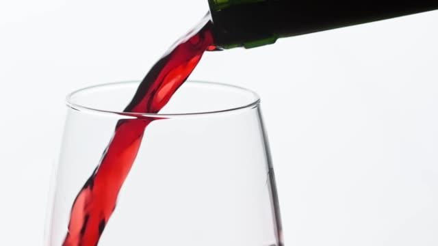 rotwein aus der flasche in den kelte gießen. nahaufnahme des weingießens in weinglas - cabernet sauvignon traube stock-videos und b-roll-filmmaterial