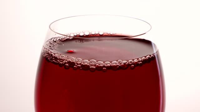 rotwein gießt aus der flasche in goblet über weißem hintergrund. rosenwein ins glas gießen. weinglas - cabernet sauvignon traube stock-videos und b-roll-filmmaterial